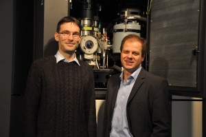Dr. Benjamin Butz and Prof. Erdmann Spiecker in front of the aberration-corrected Titan3 80-300 which was employed for the microscopic investigation of defects in bilayer graphene. (Image: FAU)
