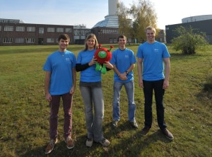 The FAU team (left to right): Tobias Netter, Raphaela Prach, Benjamin Mockenhaupt and Lukas Dresel with ESA mascot Paxi in front of the Bremen drop tower. (Image: private)