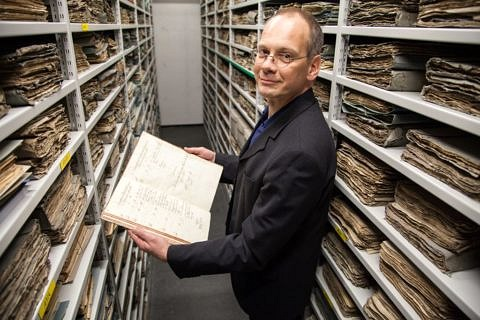 The University's archivist Dr. Clemens Wachter going through FAU's history. (Image: Georg Pöhlein)