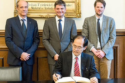 Consul General Hidenao Yanagi (front) signing FAU's Golden Book, accompanied by FAU Vice President Prof. Dr. Günter Leugering, FAU President Prof. Dr. Joachim Hornegger and Prof. Dr. Fabian Schäfer from the Chair of Japanese studies. (Image: Franziska Sponsel)