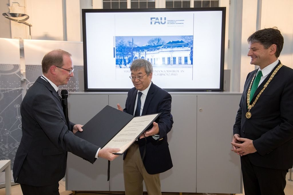 In the presence of Prof. Dr.-Ing. Joachim Hornegger, President of FAU (right), Prof. Dr.-Ing. Reinhard Lerch, Dean of the Faculty of Engineering (left), presents Prof. Fujimoto with the honorary certificate. (Image: FAU/Erich Malter)